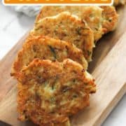 "fritters laid on a wooden board with text overlay ""potato and zucchini fritters""."