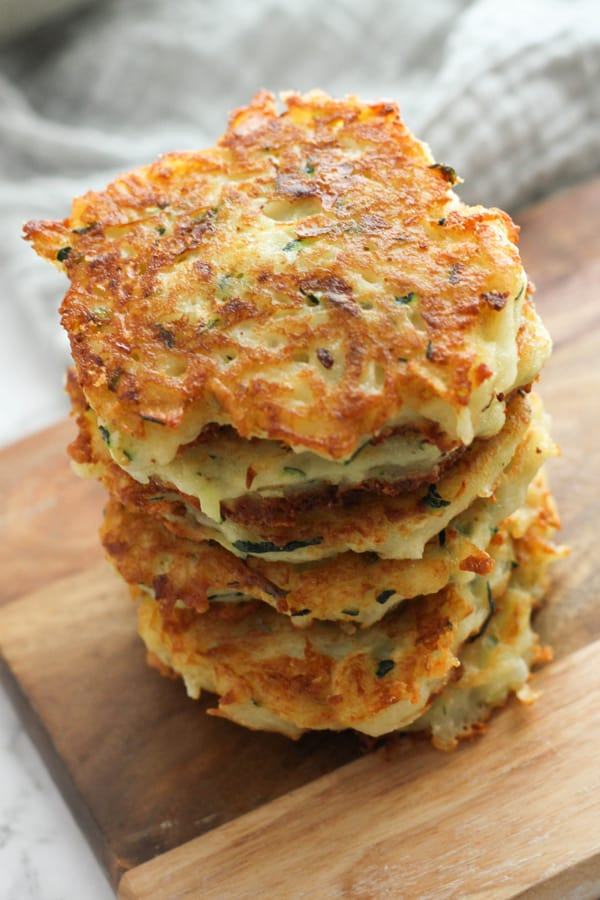 stack of potato fritters on a wooden serving bowl.