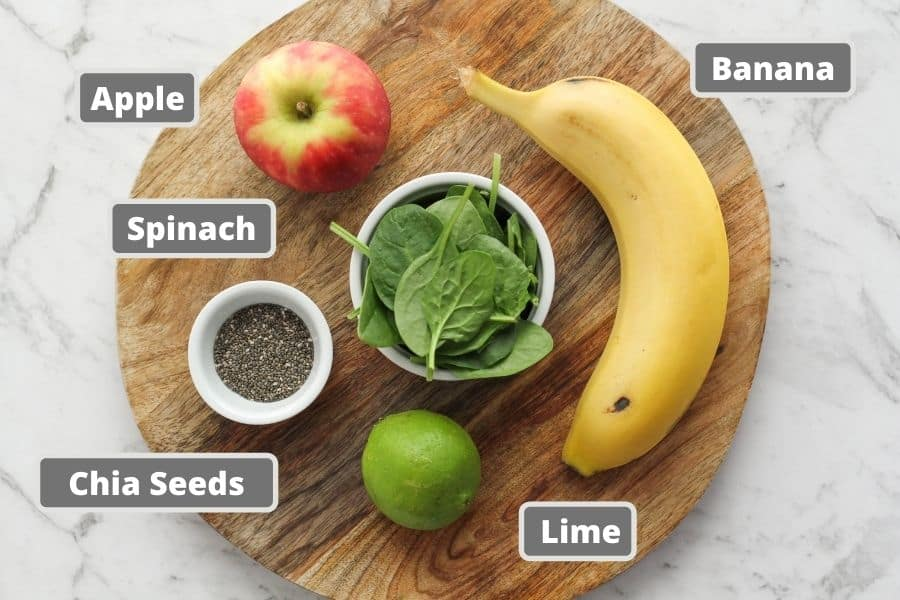 ingredients for spinach apple smoothie on a wooden board.