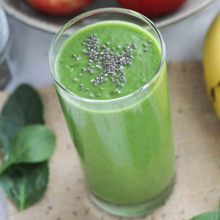 green smoothie in a tall glass topped with chia seeds.