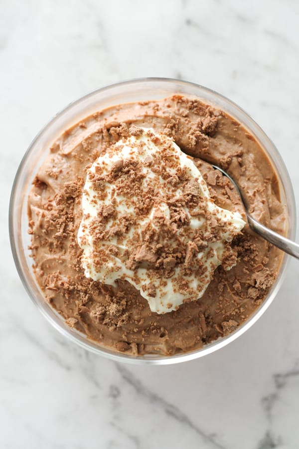 chocolate mousse in a glass topped with whipped cream and grated chocolate.
