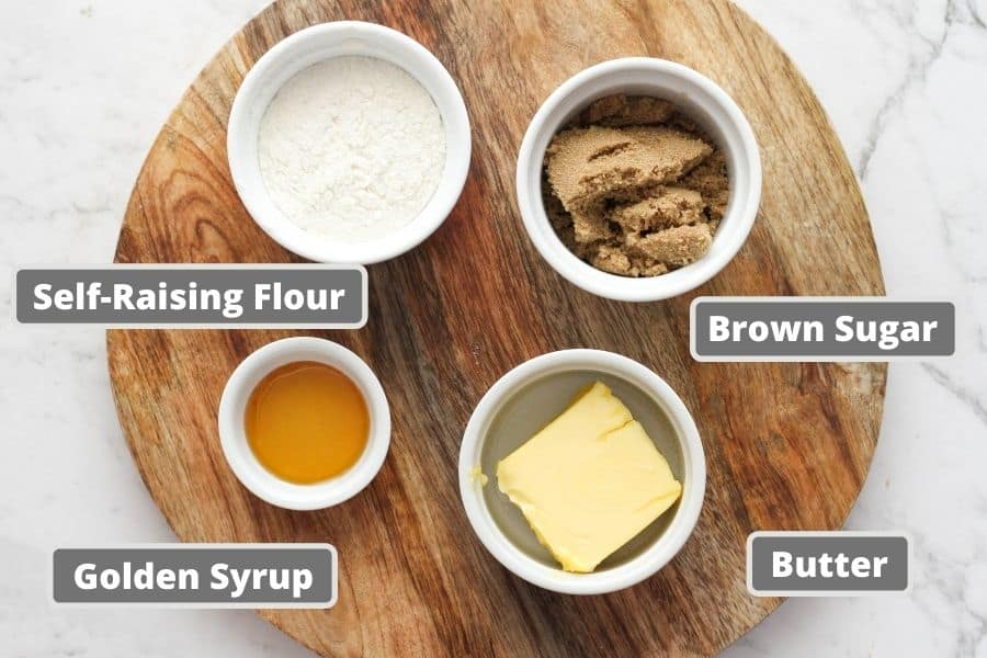 golden syrup cookies ingredients on a wooden board.