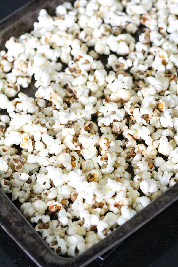 popcorn in a single layer on a baking tray.
