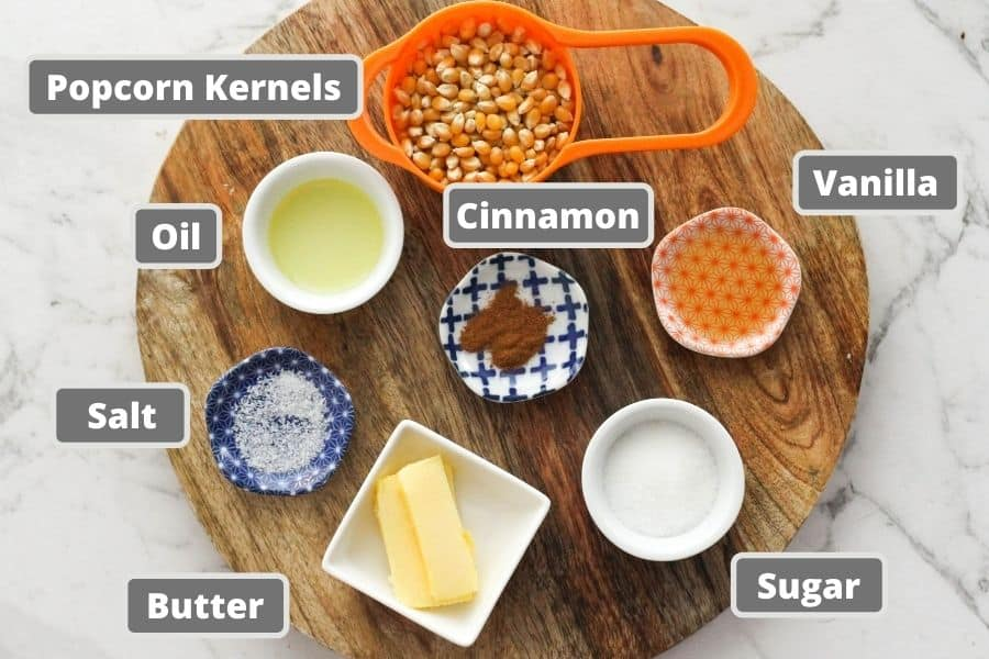 ingredients for cinnamon sugar on a wooden board including popcorn kernels, butter and sugar.