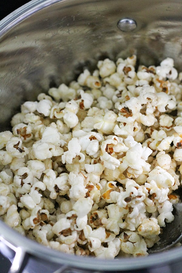 popcorn covered in butter and sugar in a saucepan.