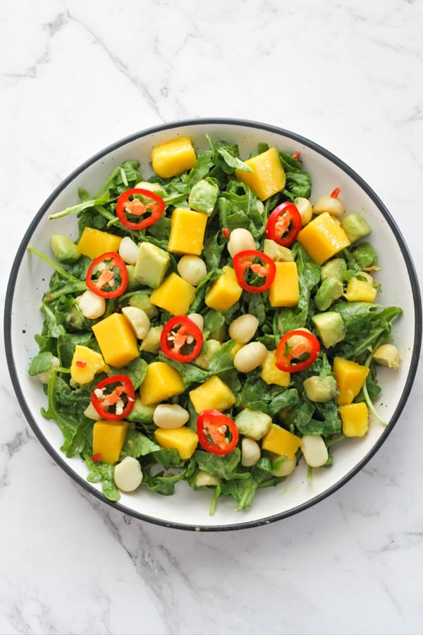 mango avocado salad in a white bowl topped with chilli slices.