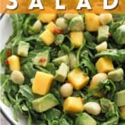 """salad in a white bowl with text overlay """"mango avocado salad""""."""