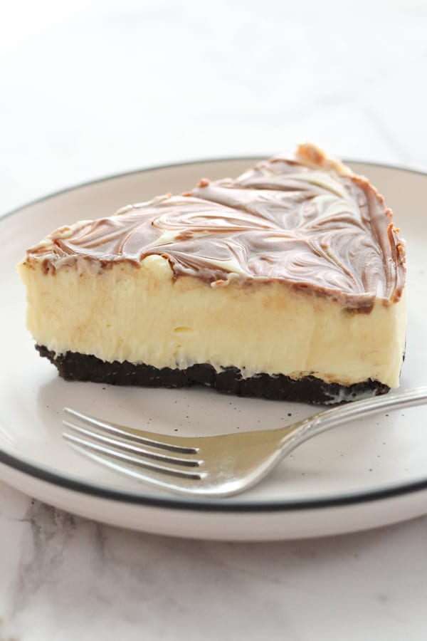 a slice of marble cheesecake with a fork on the plate.