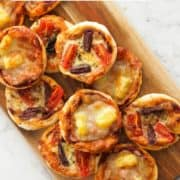"""mini pizzas on a wooden board with text overlay """"mini pizza bites""""."""