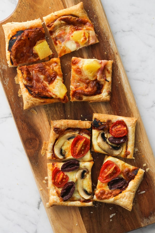 sliced puff pastry pizzas on a serving board.