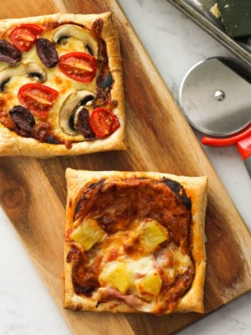 puff pastry pizzas on a wooden board.