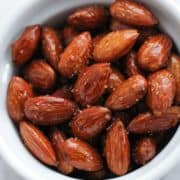 honey roasted almonds in a white bowl.