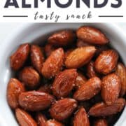"""almonds in a white bowl with text overlay """"honey roasted almonds""""."""