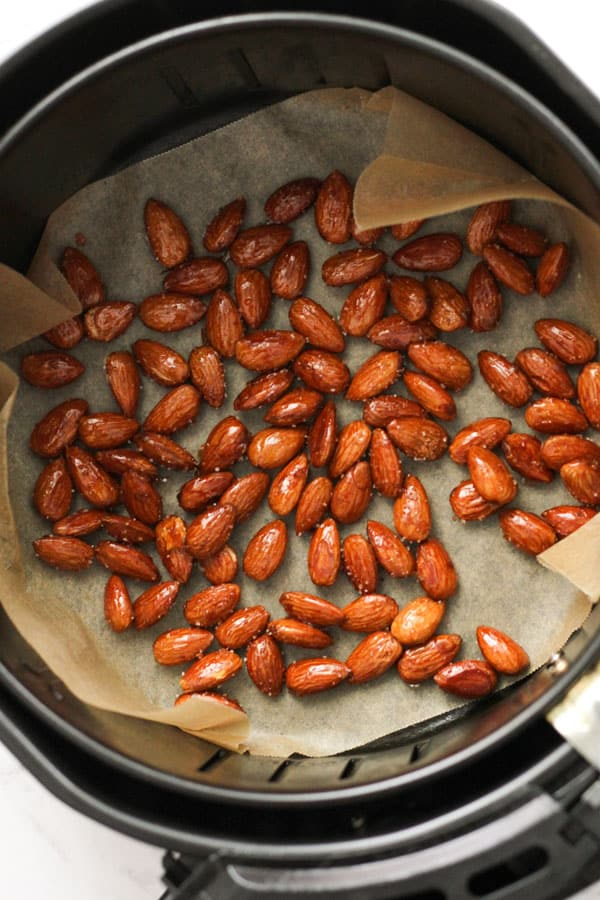 almonds in an air fryer basket.