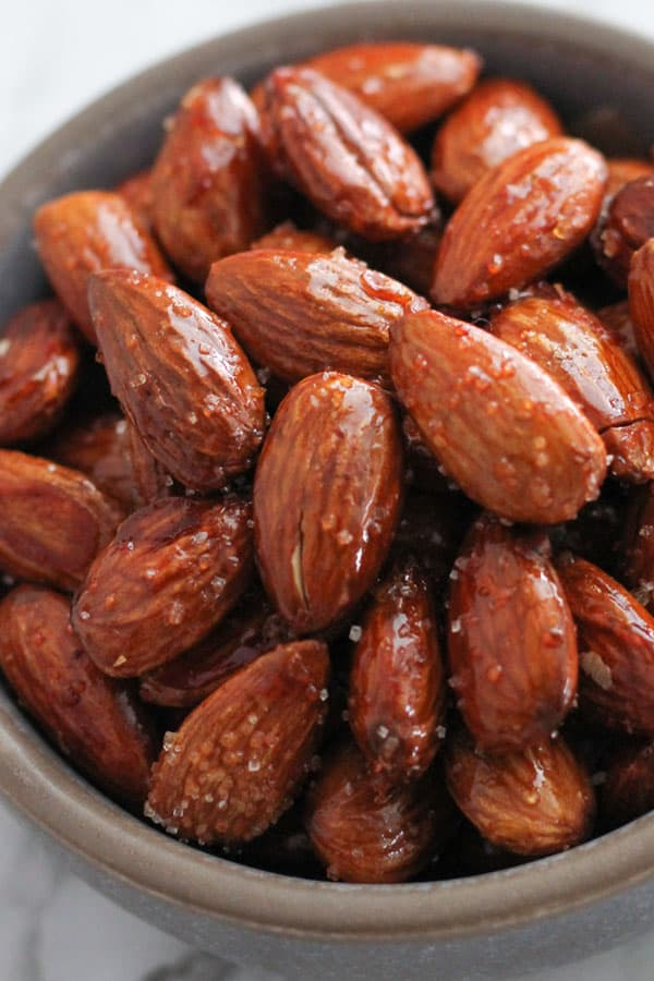 honey roasted almonds in a grey bowl.