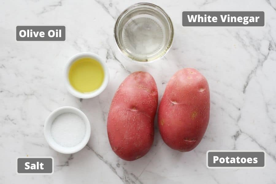 ingredients for salt and vinegar potatoes on a white marble background.