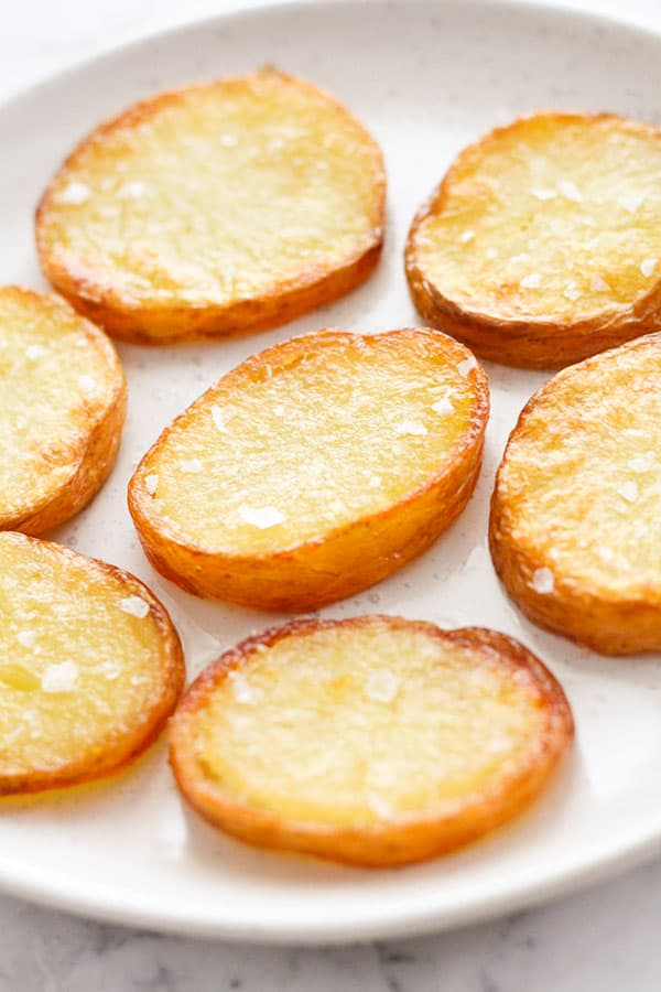 crispy salt and vinegar potatoes on a white plate.