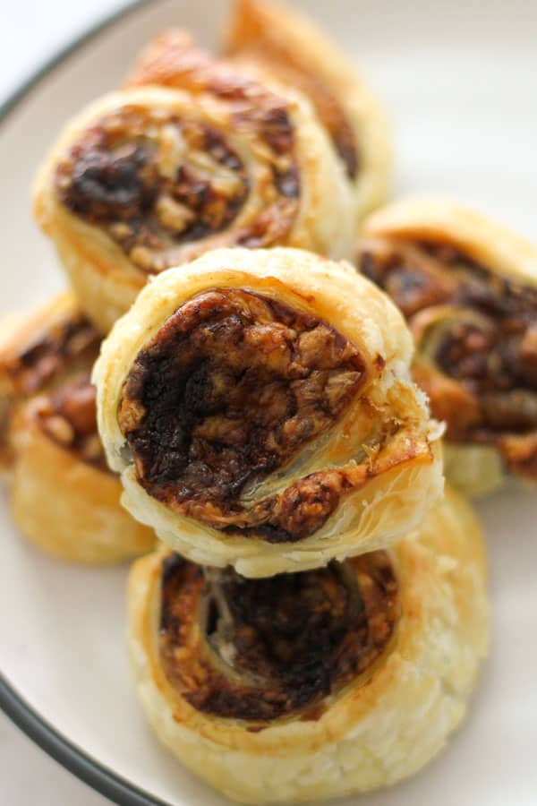 vegemite pinwheels stacked on top of each other on a white plate.