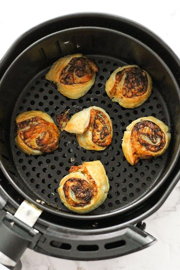vegemite and cheese pinwheels in an air fryer basket.
