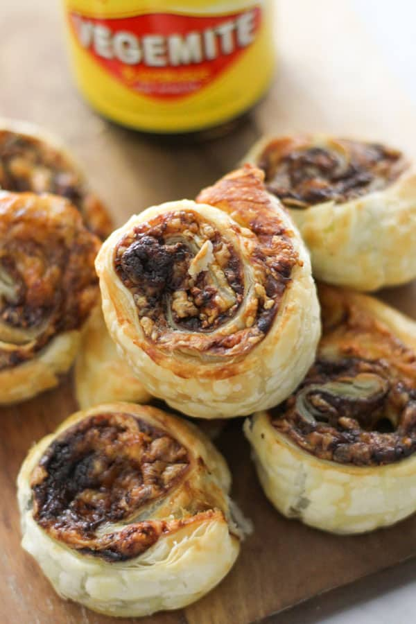 vegemite pinwheels stacked on top of each other on a wooden board.