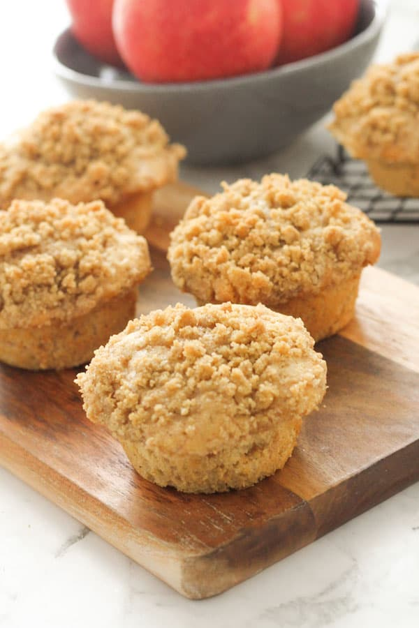 muffins on a wooden board with a bowl of apples in the background.