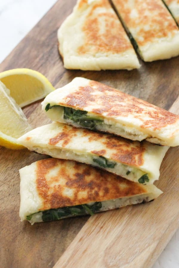 slices of spinach and feta gozleme on a wooden board.