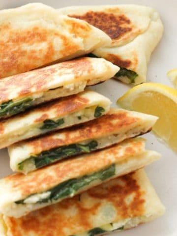 spinach and feta gozleme stacked on top of each other on a white plate.