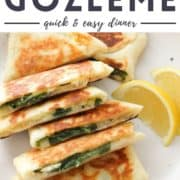 """gozleme stacked on top of each other on a white plate with text overlay """"spinach & feta gozleme""""."""
