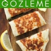 """gozleme stacked on top of each other on a wooden board with text overlay """"spinach & feta gozleme""""."""