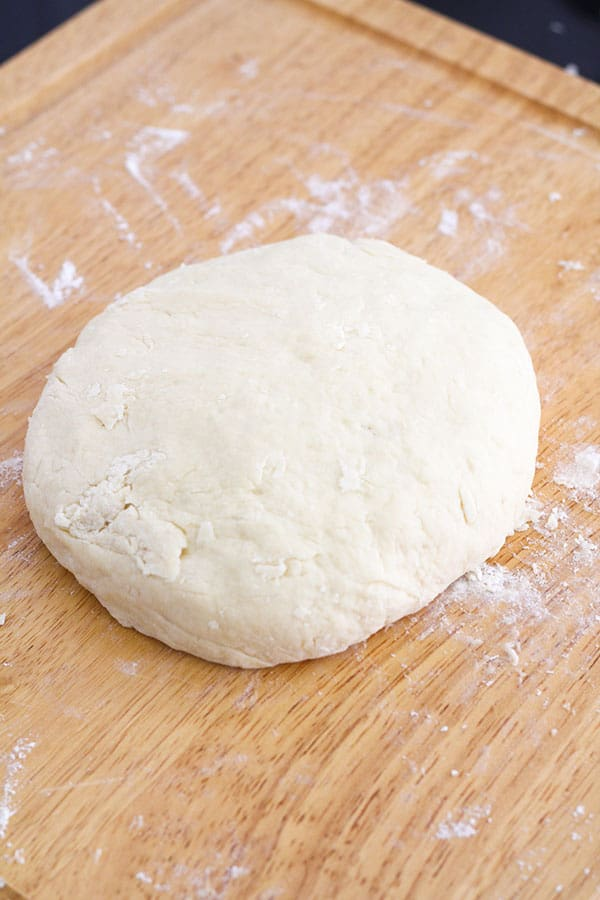 scone dough in a large disc shape on a wooden board.