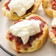 scone topped with jam and cream on a white plate.