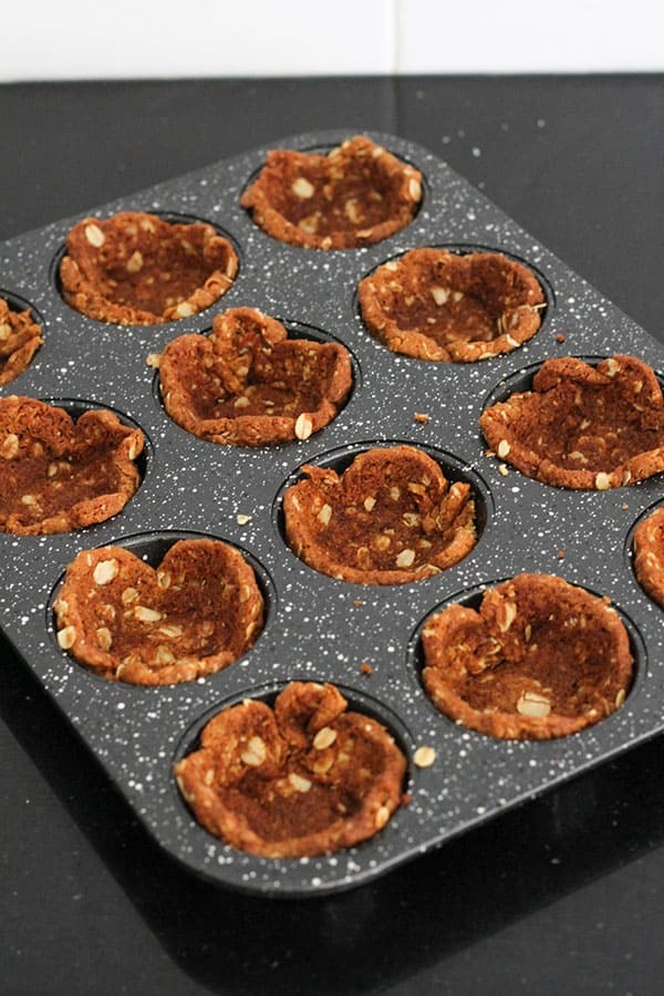 biscuits pushed into muffin tin holes to make tart cases.