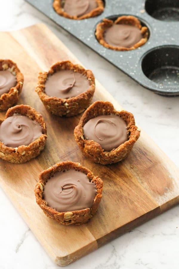 mini caramel tarts on a wooden board.