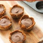 "tarts on a wooden board with text overlay ""mini chocolate caramel tarts""."
