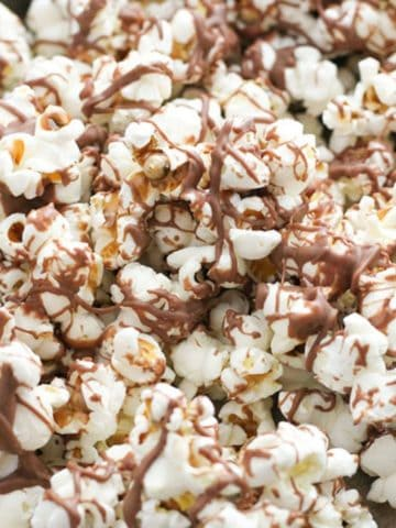 chocolate drizzled popcorn on a tray.