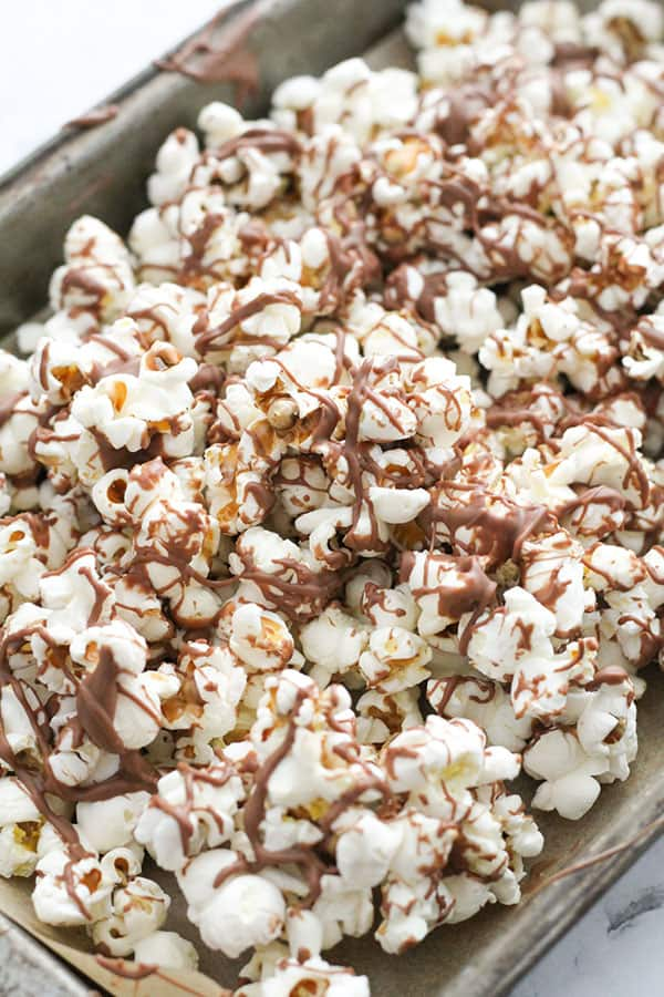 popcorn drizzled with chocolate on a baking tray.