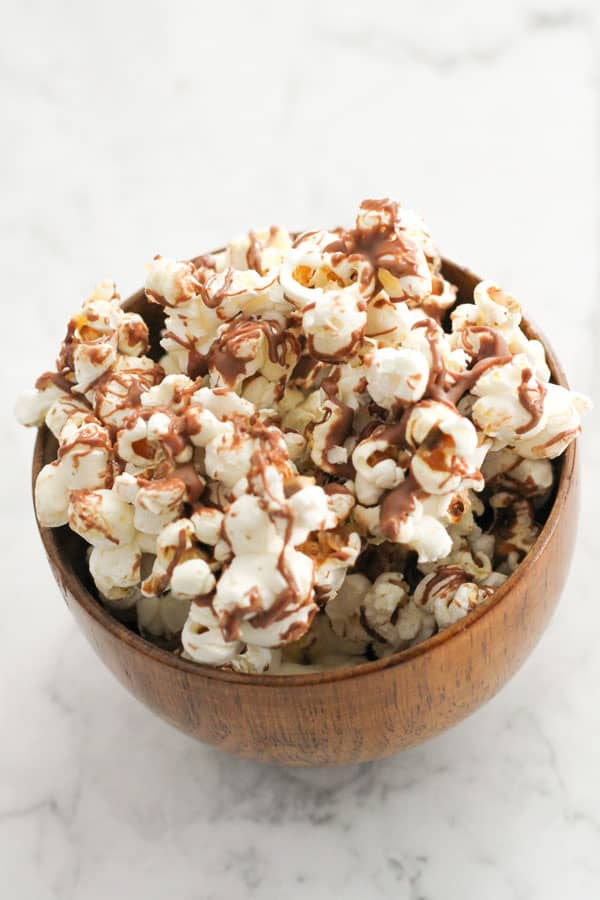 chocolate drizzled popcorn in a bowl.