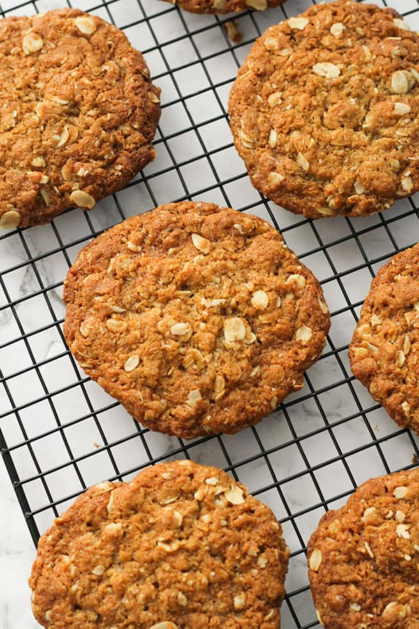 crunchy anzac biscuits on a wire rack.