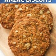 """anzac biscuits on a wooden serving board with text overlay """"crunchy anzac biscuits""""."""