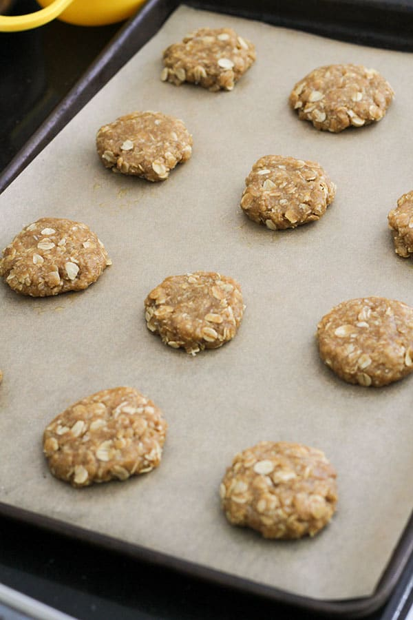 uncooked anzac biscuits on a baking tray.