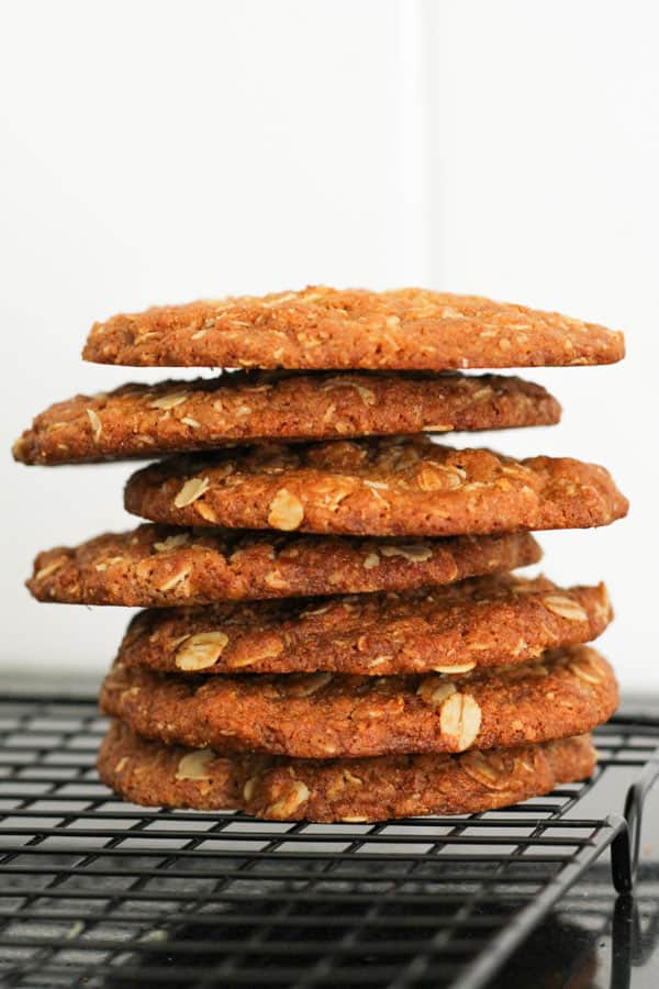 crunchy anzac biscuits stacked on a wire rack.