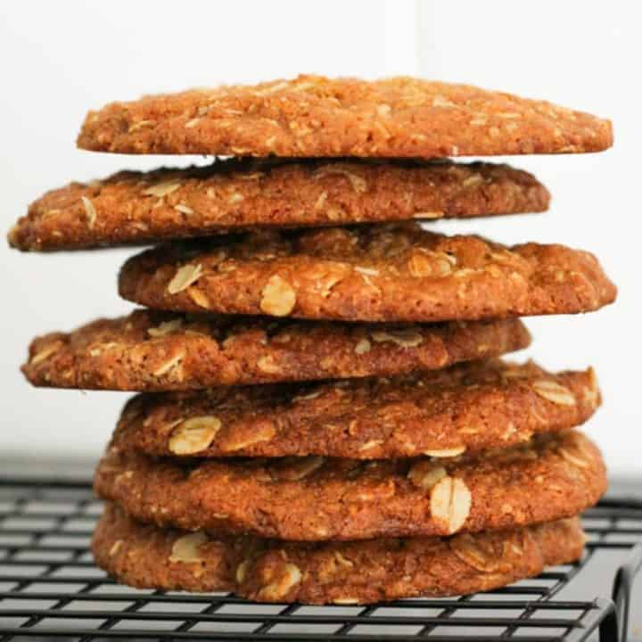 anzac biscuits stacked together on a wire rack.