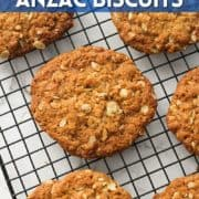 """anzac biscuits on a wire rack with text overlay """"crunchy anzac biscuits""""."""